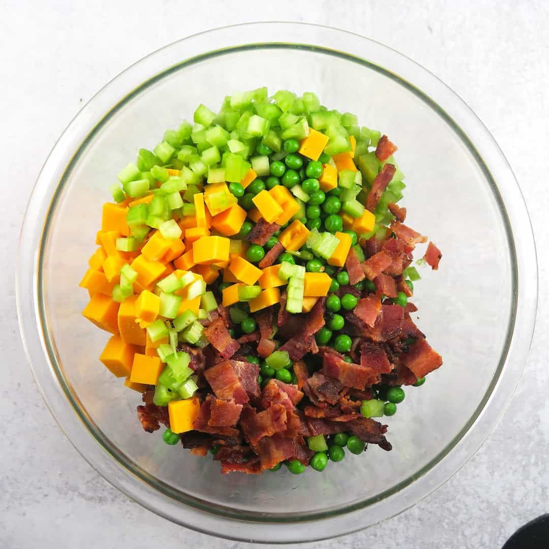 A bowl of pea salad with bacon