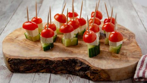 Tomato, feta, and cucumbers each neatly threaded onto a wooden skewer.