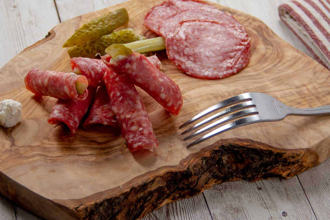 Salami presented on a wooden appetizer plate with extra pickle slices