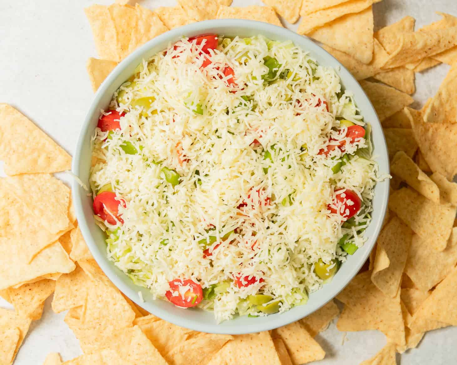 A bowl of taco dip with chips